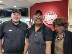 A woman with 2 men smiling at camera with Wendy's restaurant logo behind them
