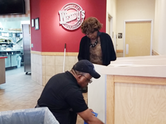Woman  helping man clean near a garbage can
