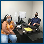 woman and man in office with masks on