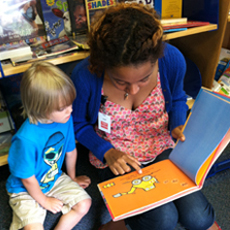 volunteer reading a book to a little boy
