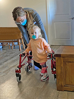 Toddler Everleigh walks with the help of a walker and Easterseals therapist