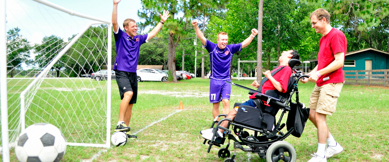man in a wheelchair playing soccer and scoring a goal