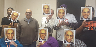 A middle-aged bald man in a brown pullover sweater stands smiling among a group of people covering their faces with headshots of the middle-aged man.
