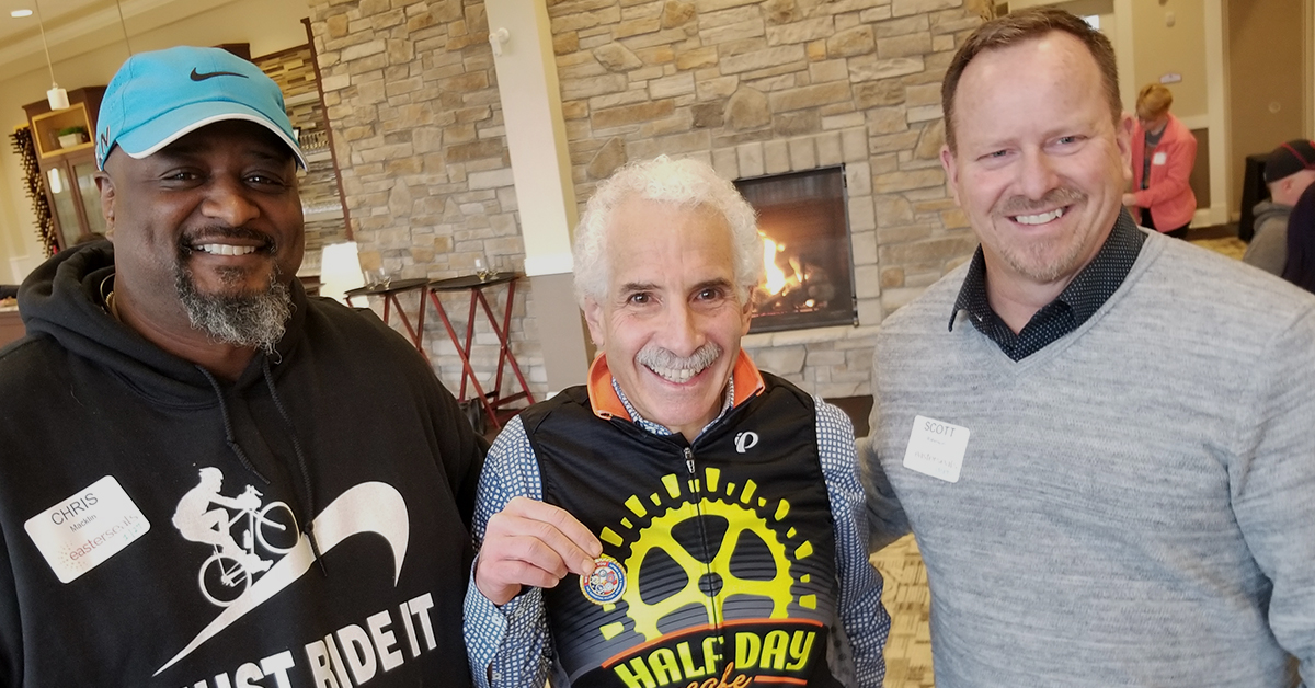 Scott Litwin (center) of the Wyoming Ohio Cycling Foundation accepts a challenge coin from Easterseals Military and Veterans Services staffers Chris Macklin and Scott Robinson