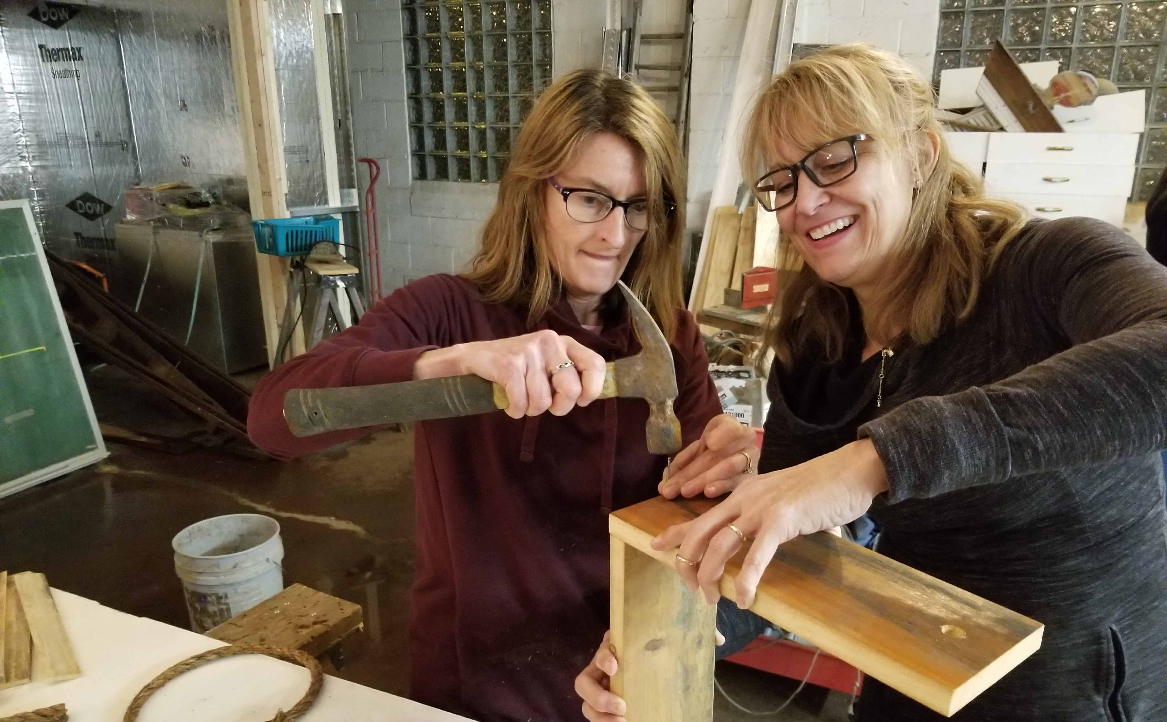 Women building wine caddy at Building Value DIY Workshop