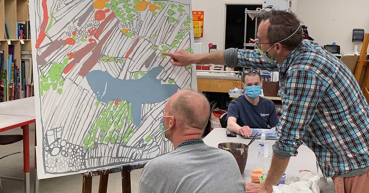 Artist Brett Garrett of Hamilton consults with InsideOut Studio art education coordinator Stephen Smith on his painting. Brett recently placed third in the statewide