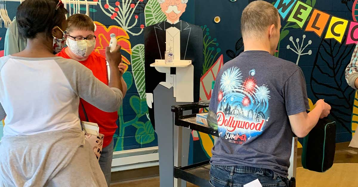Artist Allison Davis completes a health screening the lobby of InsideOut Studio with support staff member Terri Elms.