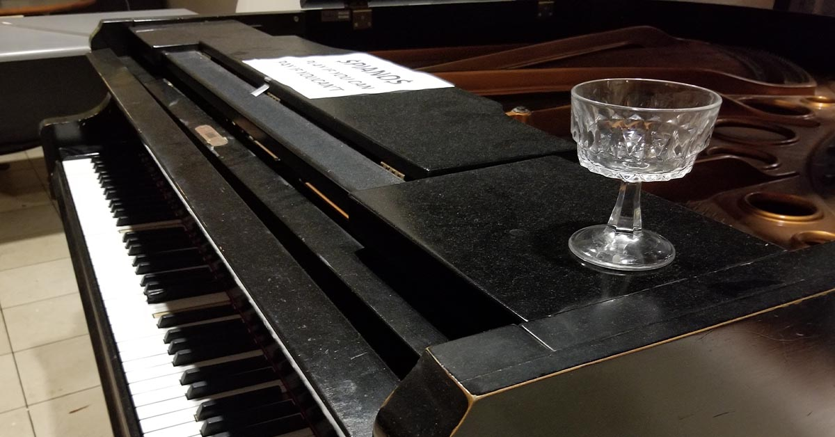 A lone cocktail glass sits atop a grand piano.