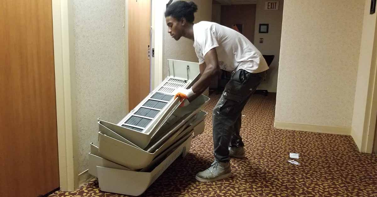 Building Value employee Jah stacks AC unit covers in the hallway.