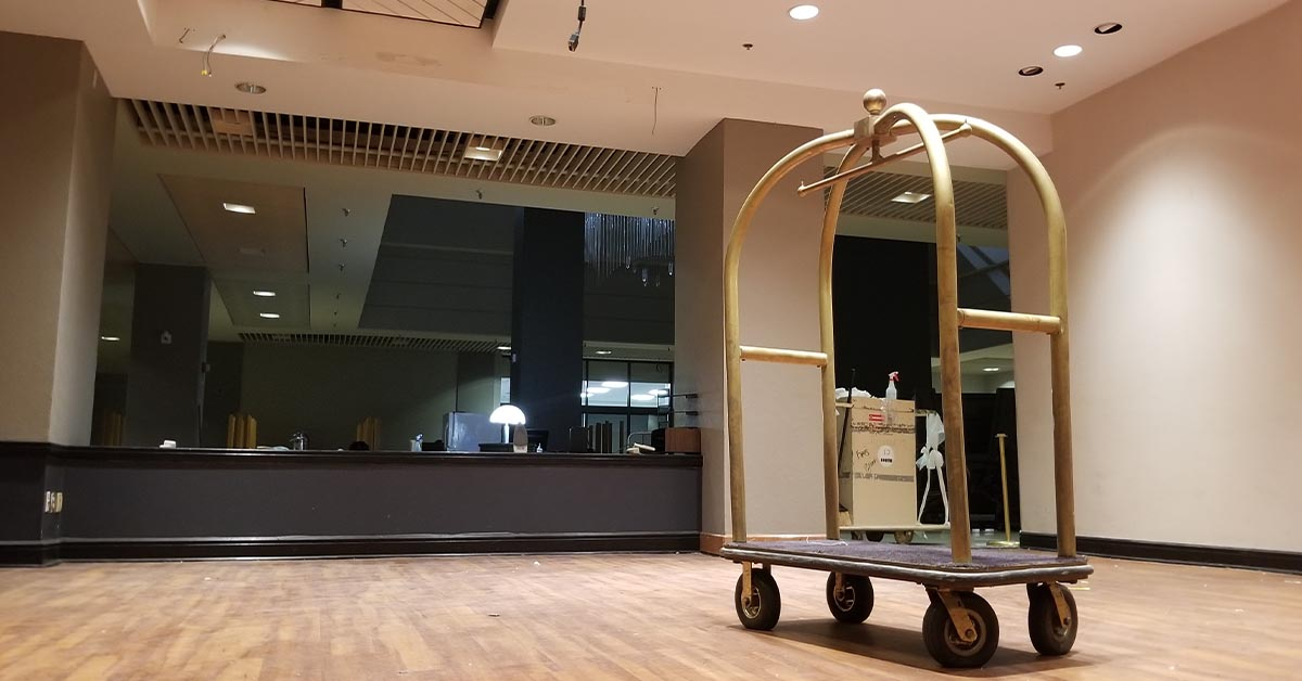 A single luggage cart sits in the middle of a vacant lobby area.