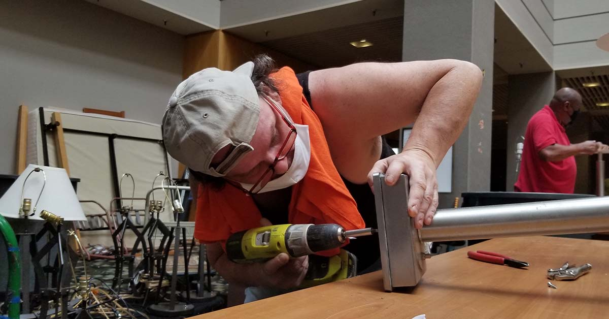 Robert removes the bases from table lamps to prepare them for recycling.