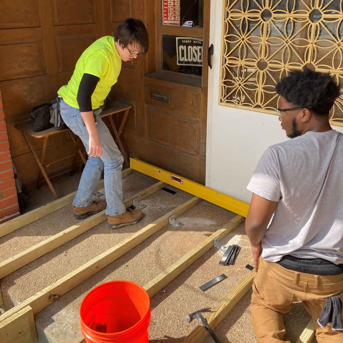 Meghan and Jude from Easterseals YouthBuild check the level on their construction work.