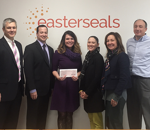 Six professionals stand in front of the Easterseals logo, smiling. One woman in the center displays the gift check.