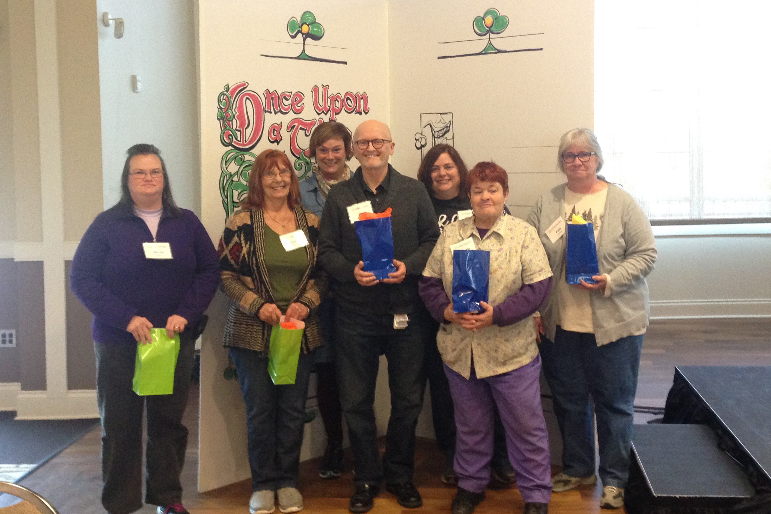 A group of adults smile while holding gift bags celebrating work anniversaries