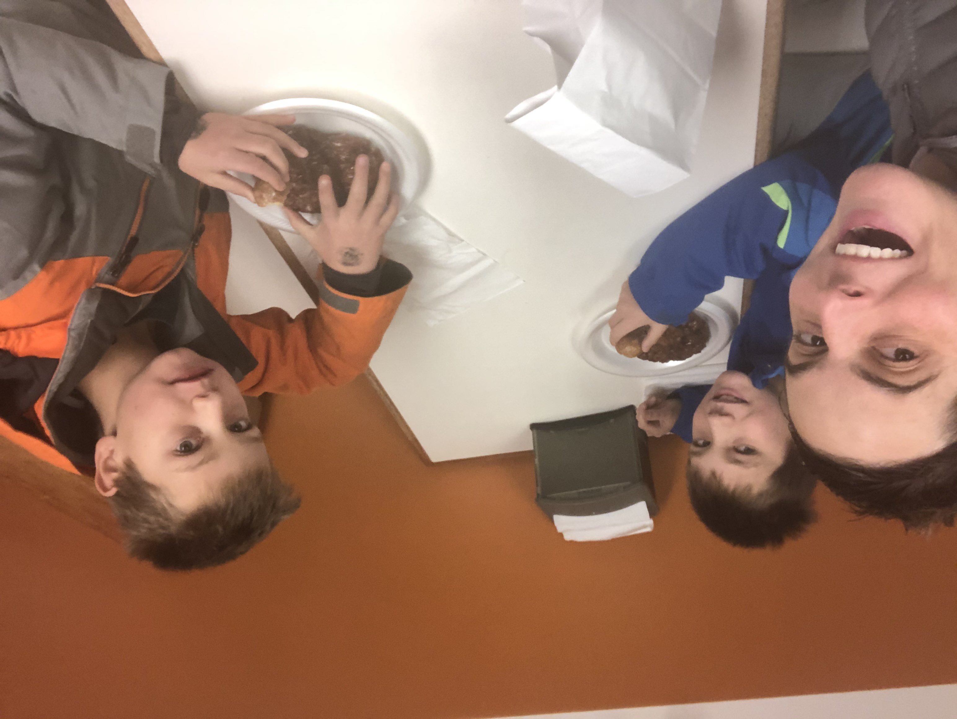 Mom and two sons eating donuts