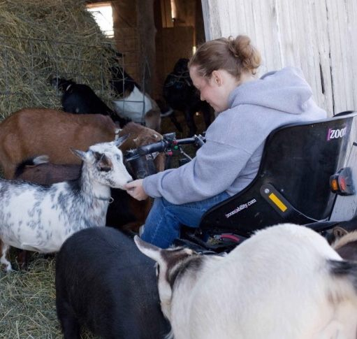 Renae tending to goats on her farm while using her Zoom accessibilty device