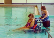 Pool staff uses an aquatic wheelchair to assist clients with disabilities.