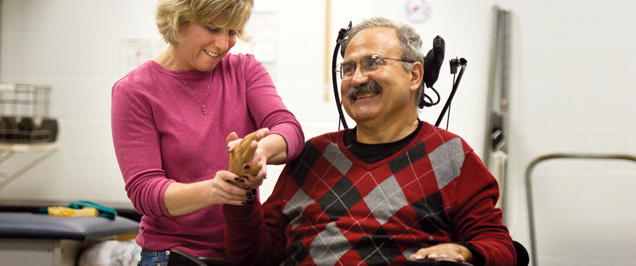 man with a disability smiling while a woman grabs his hand