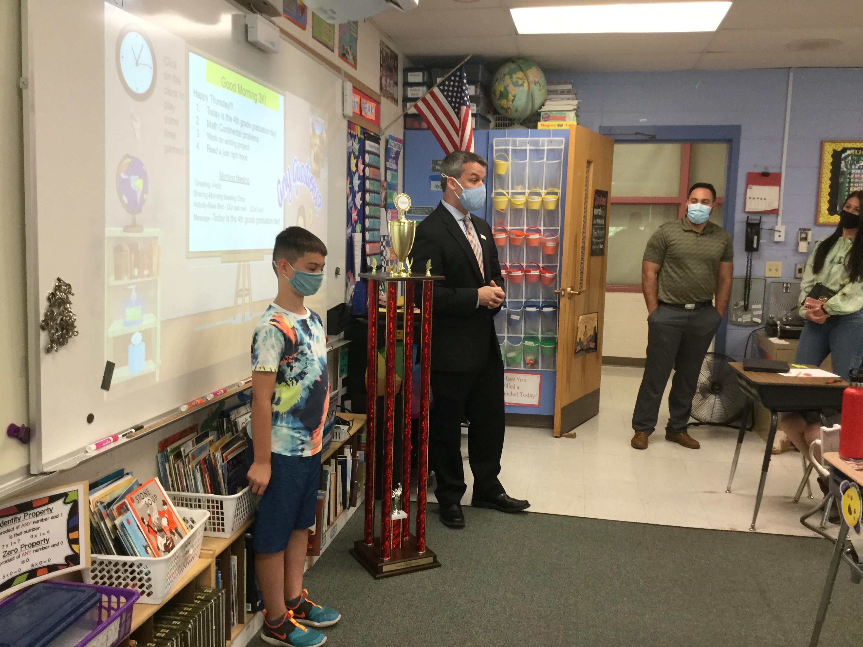Paul speaks to Joey's class inside the classroom before awarding him