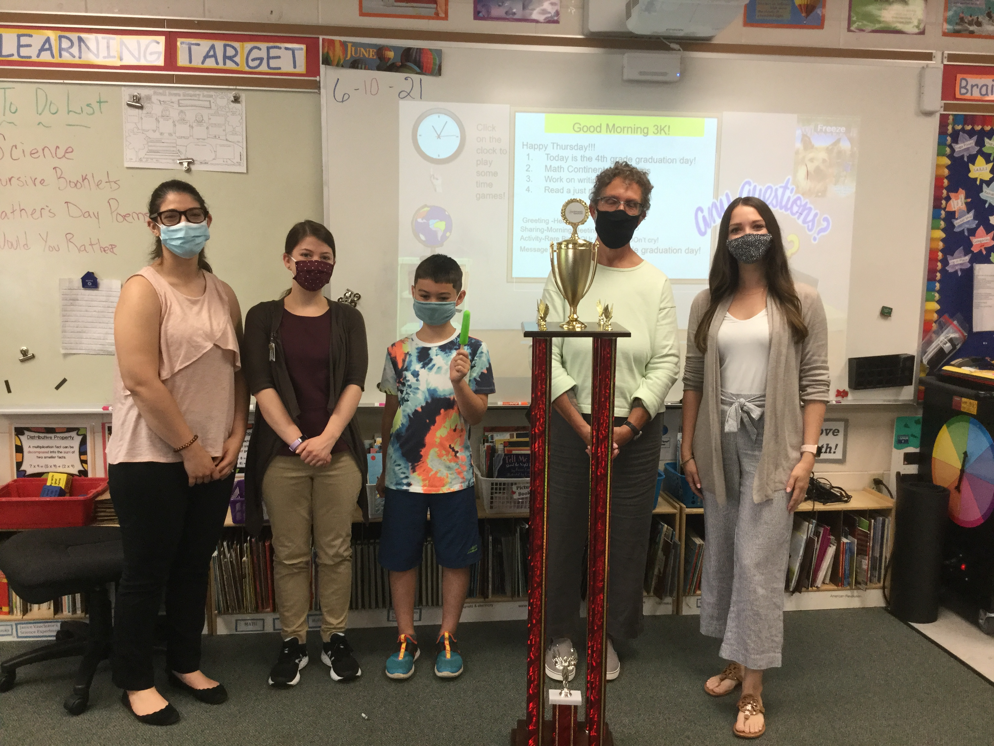 Joey stands with his teachers and Kristi, AT Specialist, at the front of the classroom after receiving the 2021 Pioneer Award