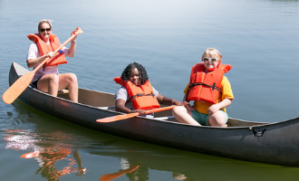 two campers with disabilities sit in a canoe paddled by a camp counselor on the water.