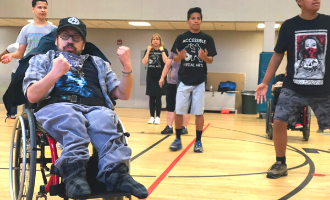 A man in a wheelchair participates in an accessible martial arts class, holding out his fists