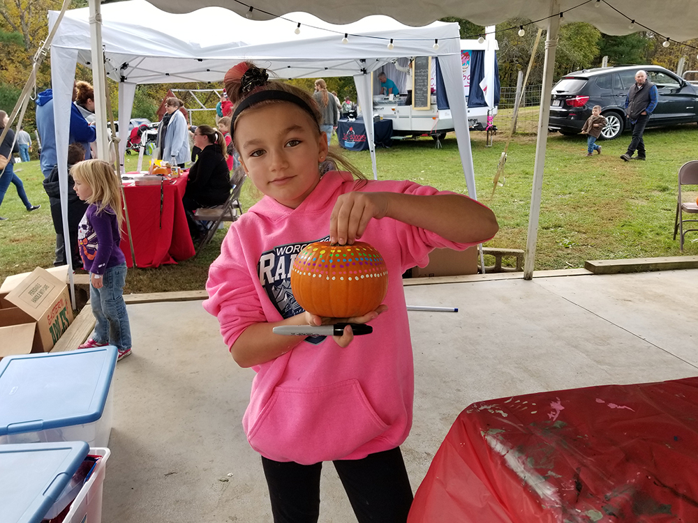 A young girl smiling and showing a pumpkin she painted