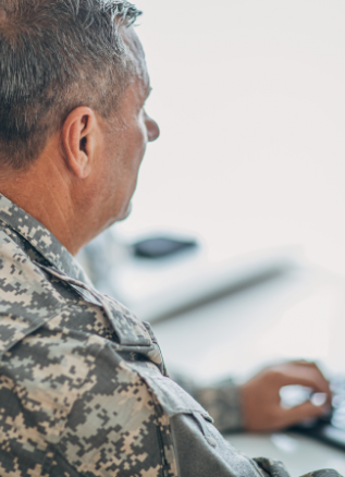 a male veteran sits in uniform at a computer