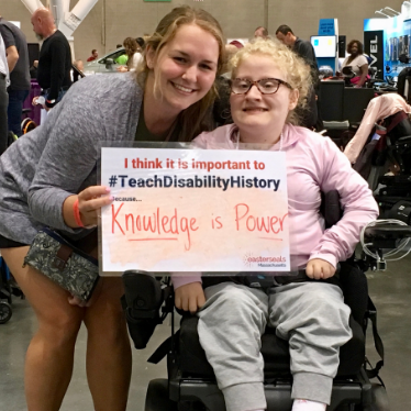 two women holding a sign that reads i think it is important to teach disability history because knowledge is power