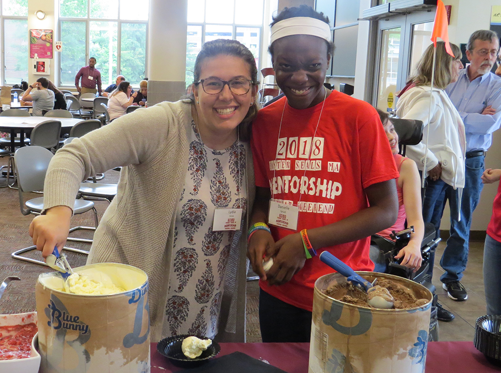 A mentor and a young woman from the female mentoring program smiling while scooping ice cream