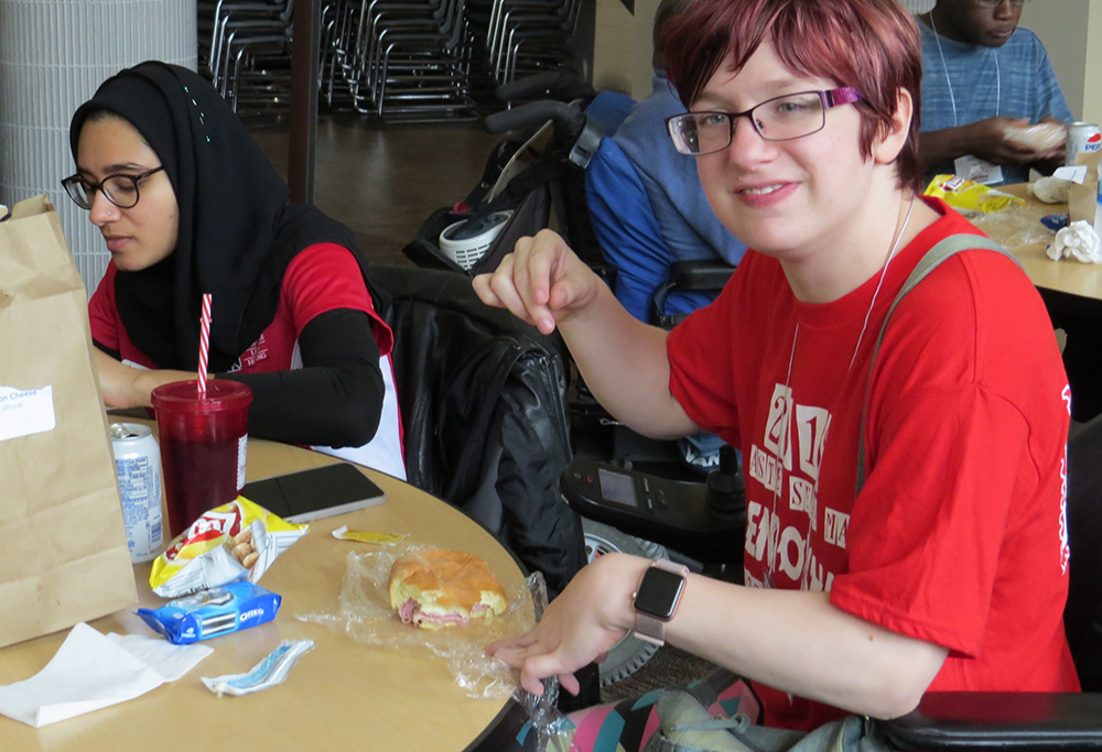Two young women eating at a lunch table. One is smiling at the camera.