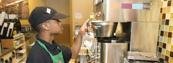 A person with a disability wears an apron & operates a coffee machine in a coffee shop