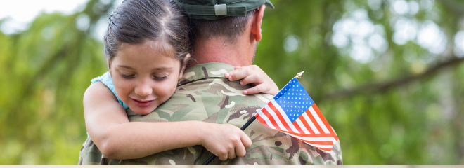 a person in military uniform holds up a young girl, hugging her as she smiles and holds an American flag