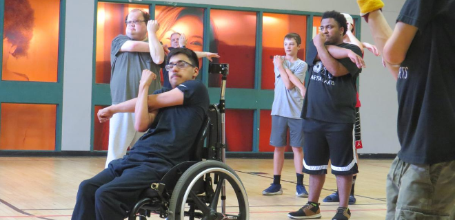 Young adults with disabilities practicing adaptive stretching before an accessible martial arts class.