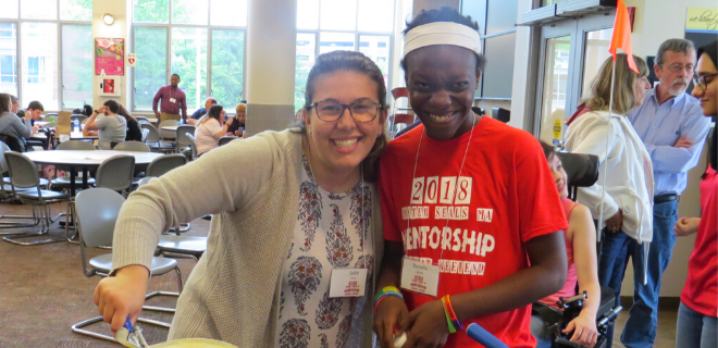 A young adult with disabilities standing near her mentor at a mentorship event