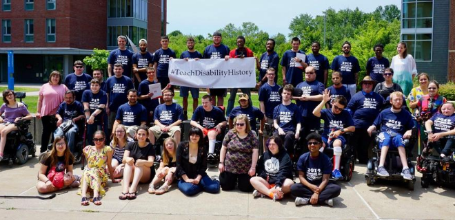 a group of youth leadership network participants standing together holding a sign that reads #TeachDisabilityHistory