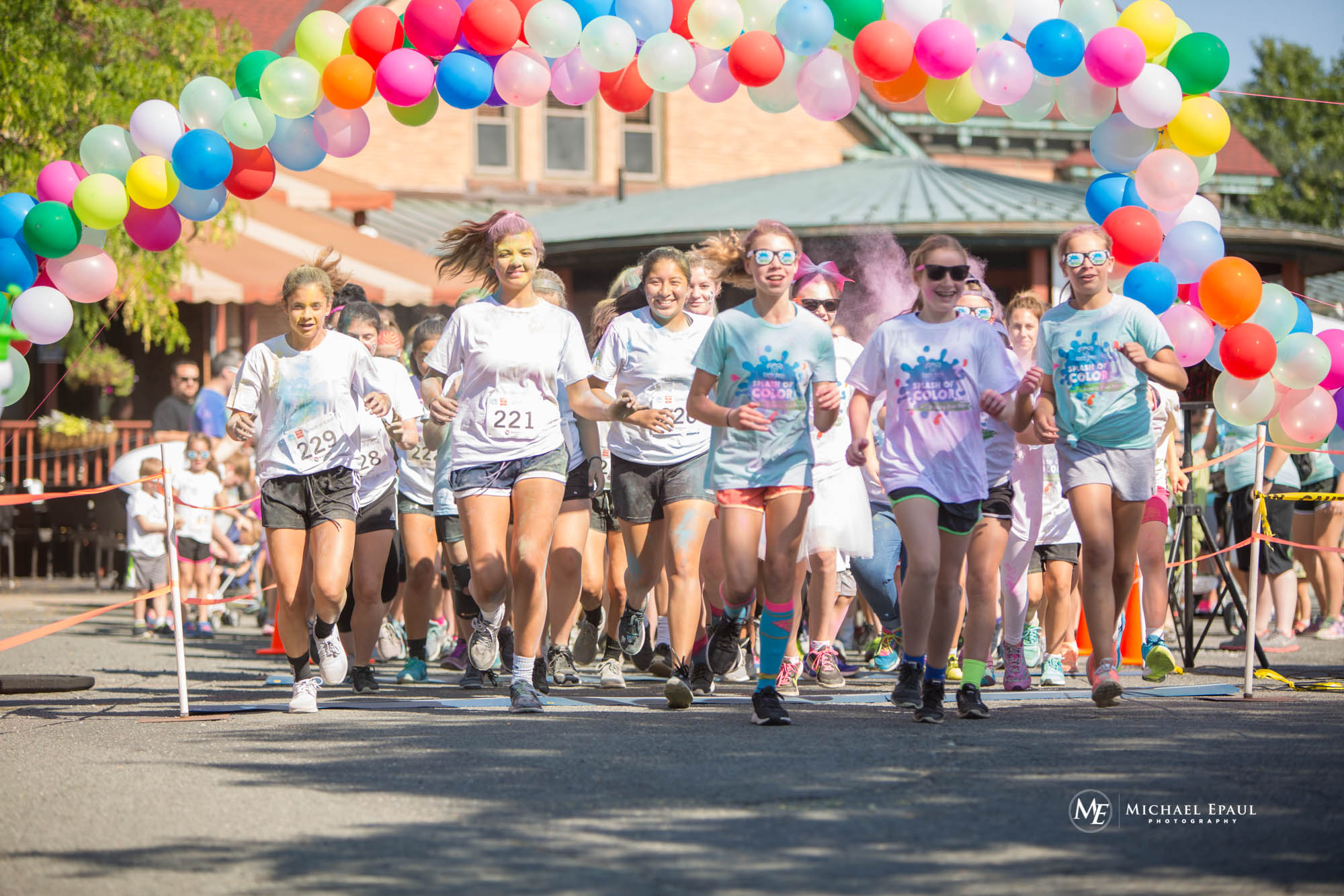 A large group of runners beginning the 5 k race at the starting line, which features a colorful balloon arch