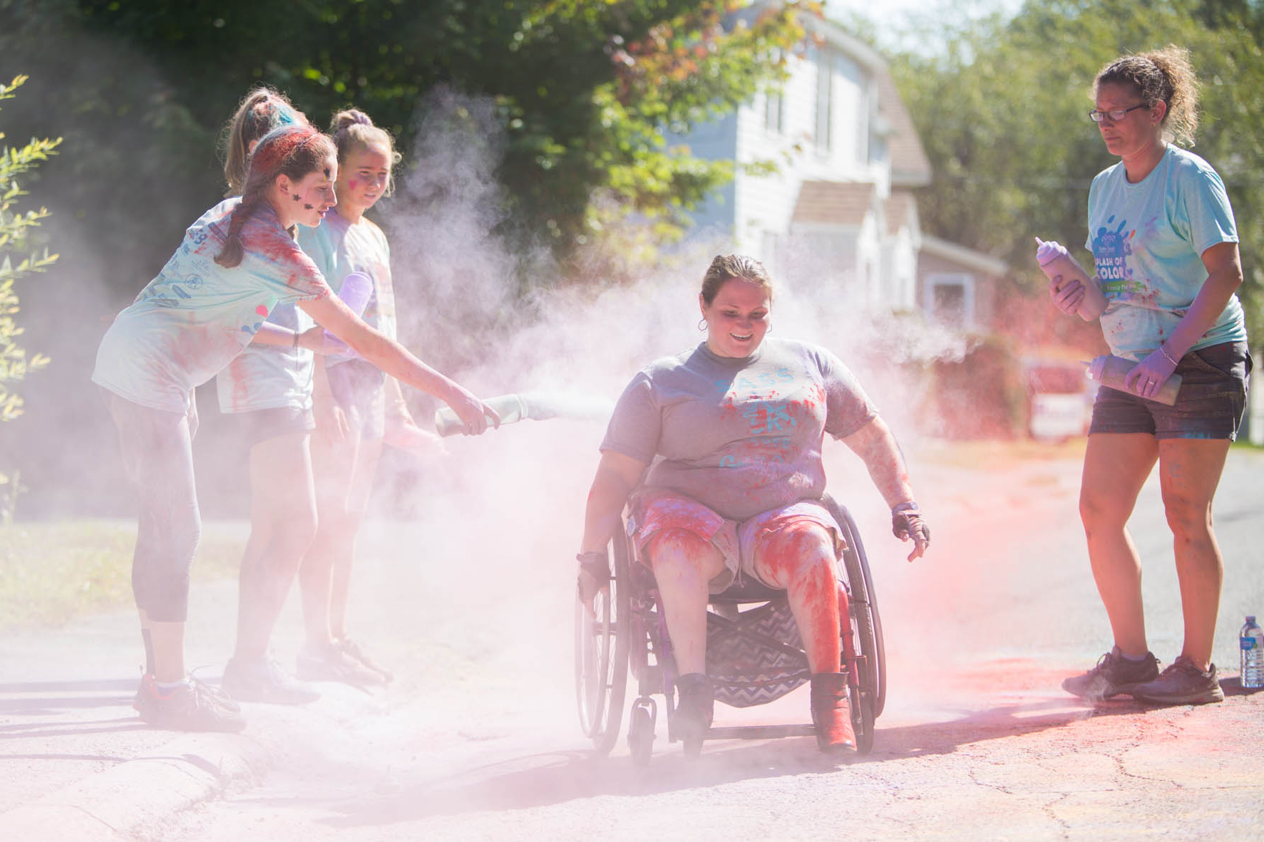 A participant using a wheelchair having colorful dust thrown on her