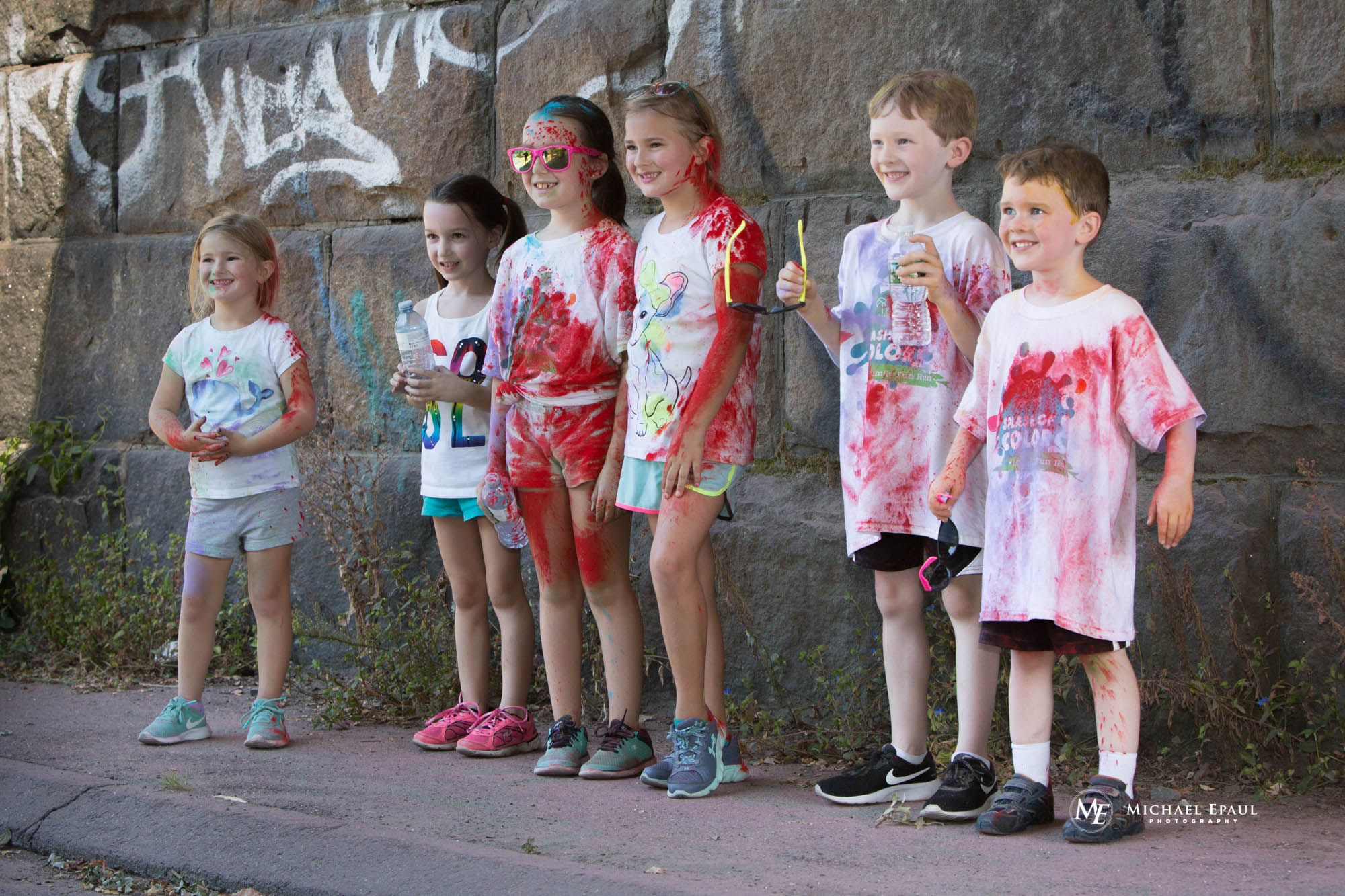 A group of young children standing in front of a brick wall smiling. They are covered in colorful dust.