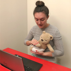 Shannon, a Rehabilitation Therapist, demonstrates for a client using a laptop