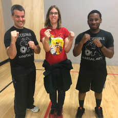 Abby stands next to President & CEO Paul Medeiros and Program Leader Patrick Remy, all with fists up in a martial arts stance