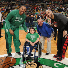Sandy Ho sits on the center of the Celtics' court at TD Garden next to Celtics players and staff