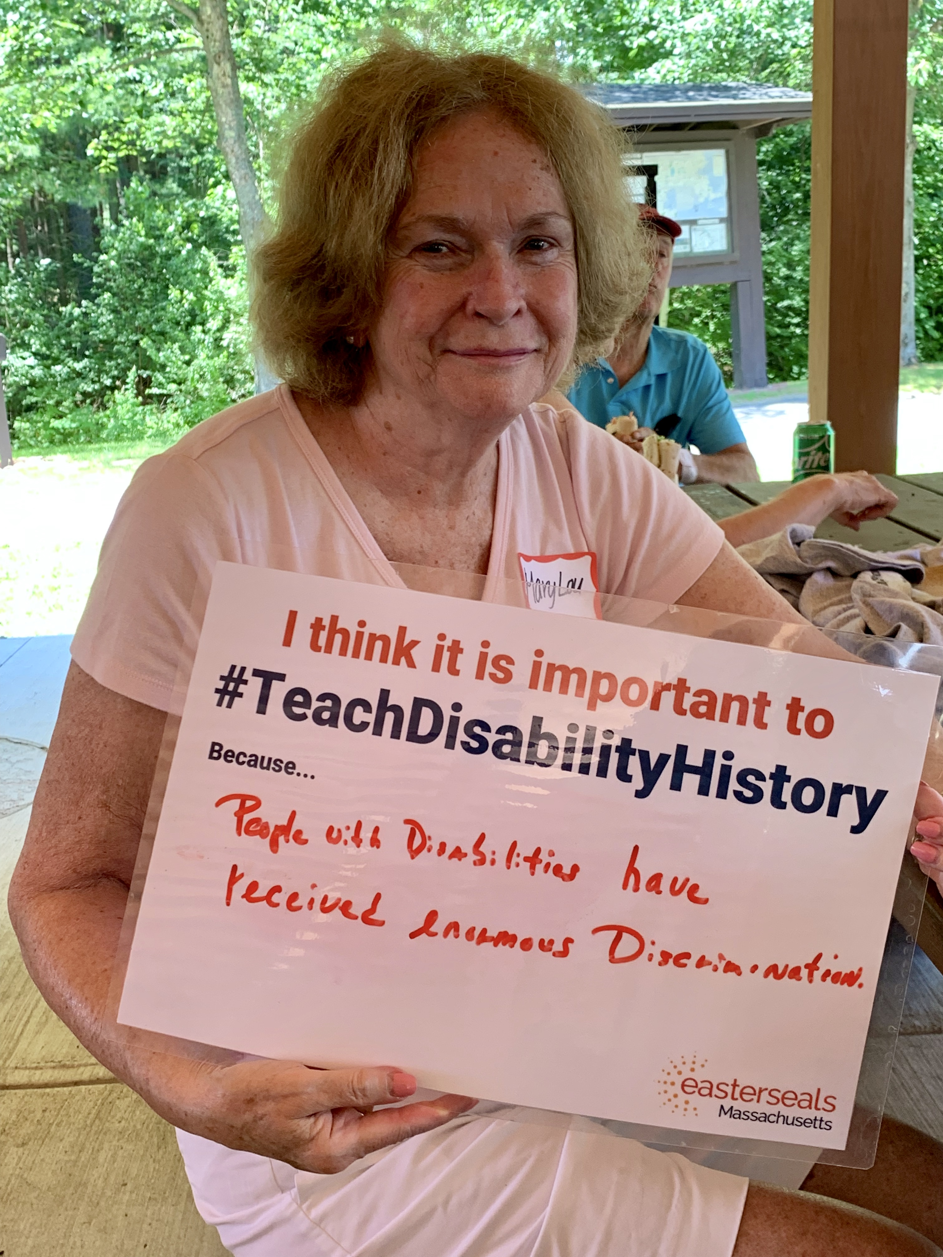 Woman sitting outside holding a sign that reads I think it is important to #TeachDisabilityHistory because