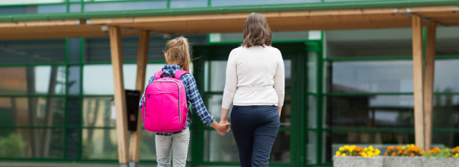 A young girl wears a pink backpack while holding hands with her mother, walking towards a school