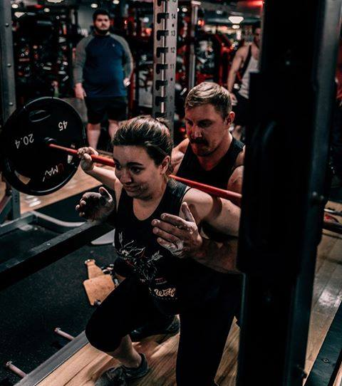 Jake assists a woman in lifting heavy weights inside a gym