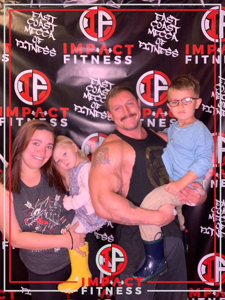 Jake Webb with his wife and two kids at the 1000/500 lb Club Fundraiser at Impact Fitness, which he helped organize.