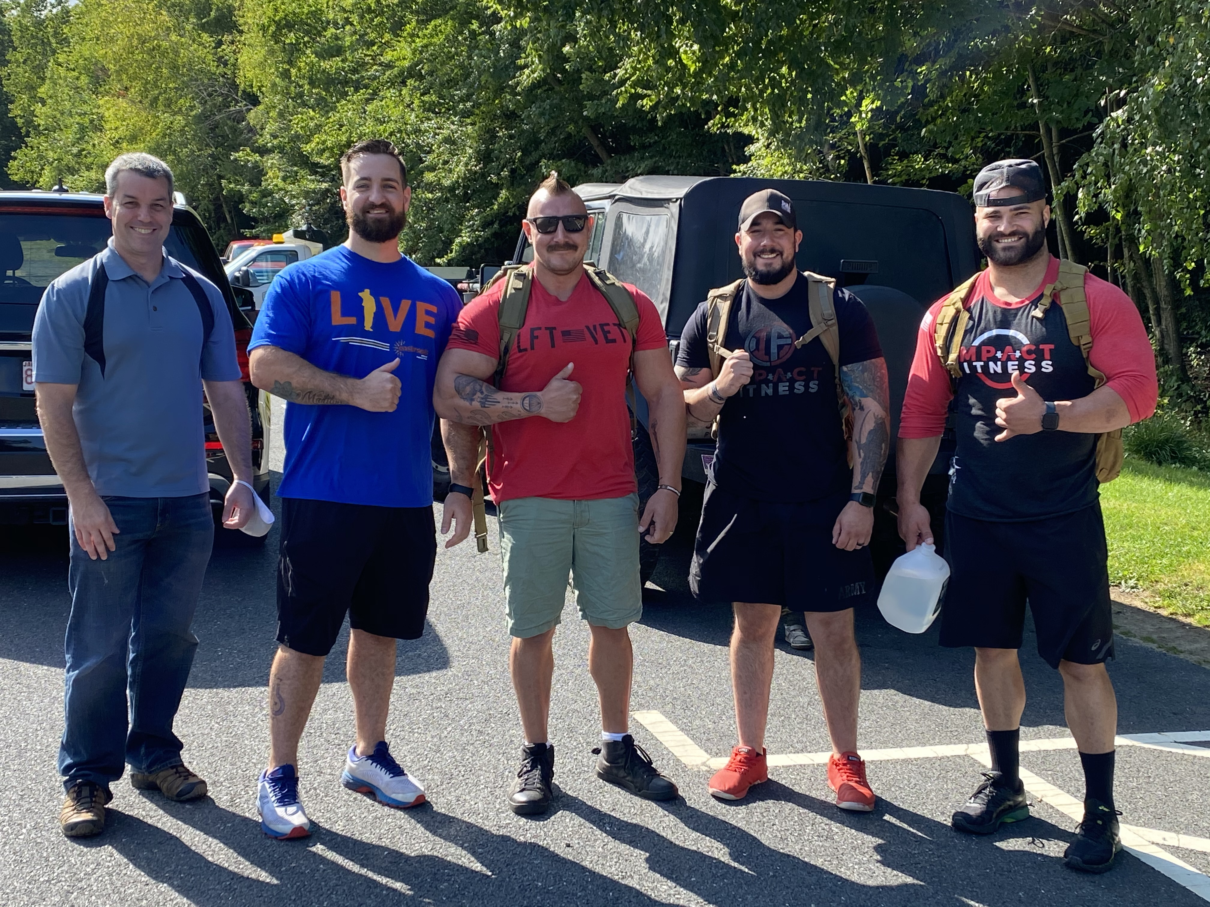 Jake Webb stands with four other men holding their thumbs up before beginning a hike.
