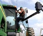 Man getting lifted into tractor