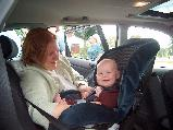 Mother putting baby in car seat