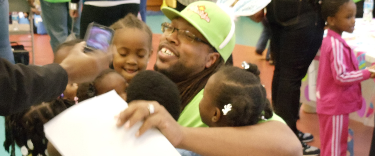 smiling man being greeted by a number of smiling children